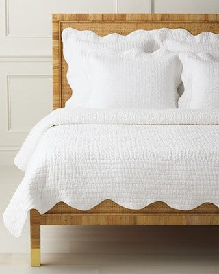 white scalloped quilt on rattan bed
