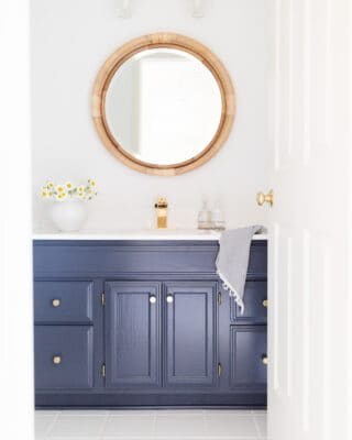 navy and white nautical bathroom with rattan mirror
