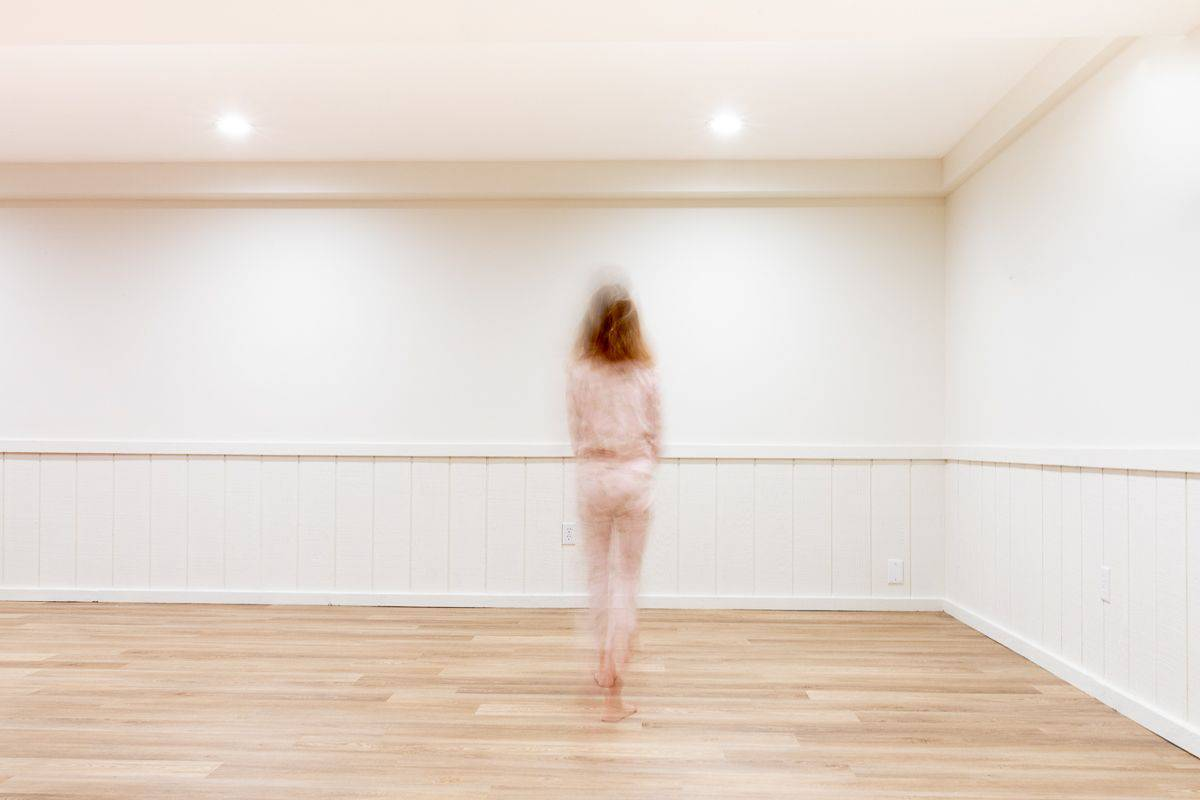 A freshly painted basement with LRV floors and Benjamin Moore Swiss Coffee painted on the walls, a girl walking.