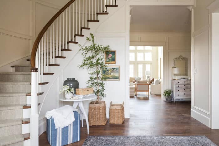 A warm white entrance with a curved staircase, painted in the Swiss café Benjamin Moore.