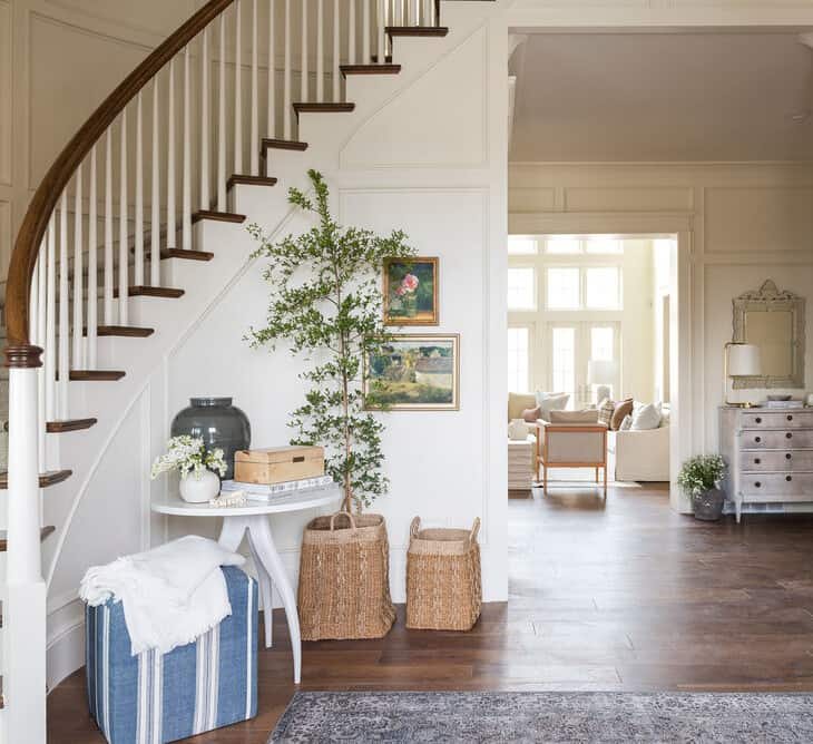 A warm white entryway with a curved staircase, painted in Benjamin Moore Swiss Coffee.
