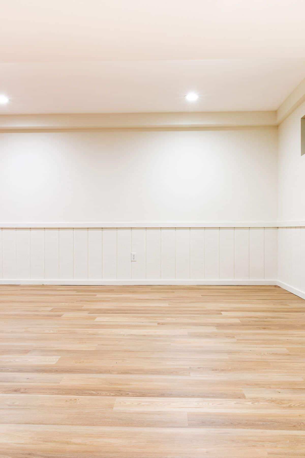 A newly painted basement with LRV floors and Benjamin Moore Swiss coffee paint on the walls