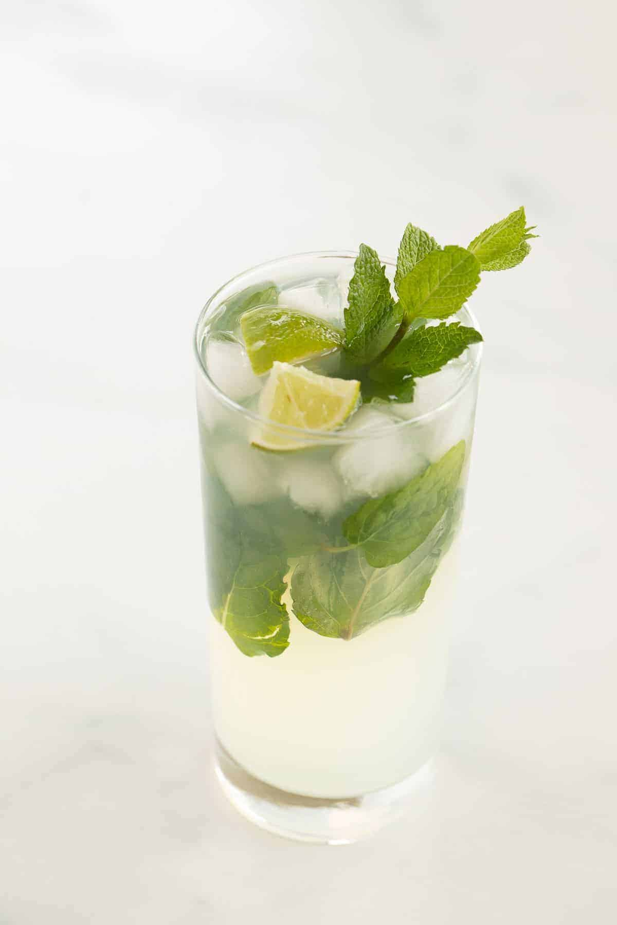 A tequila mojito in a clear glass on a white surface, garnished with wedges of lime and fresh mint.