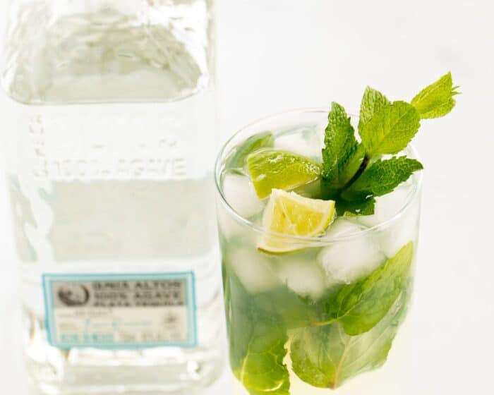 A tequila mojito in a clear glass on a white surface, garnished with lime wedges and fresh mint, bottle of tequila in the background.