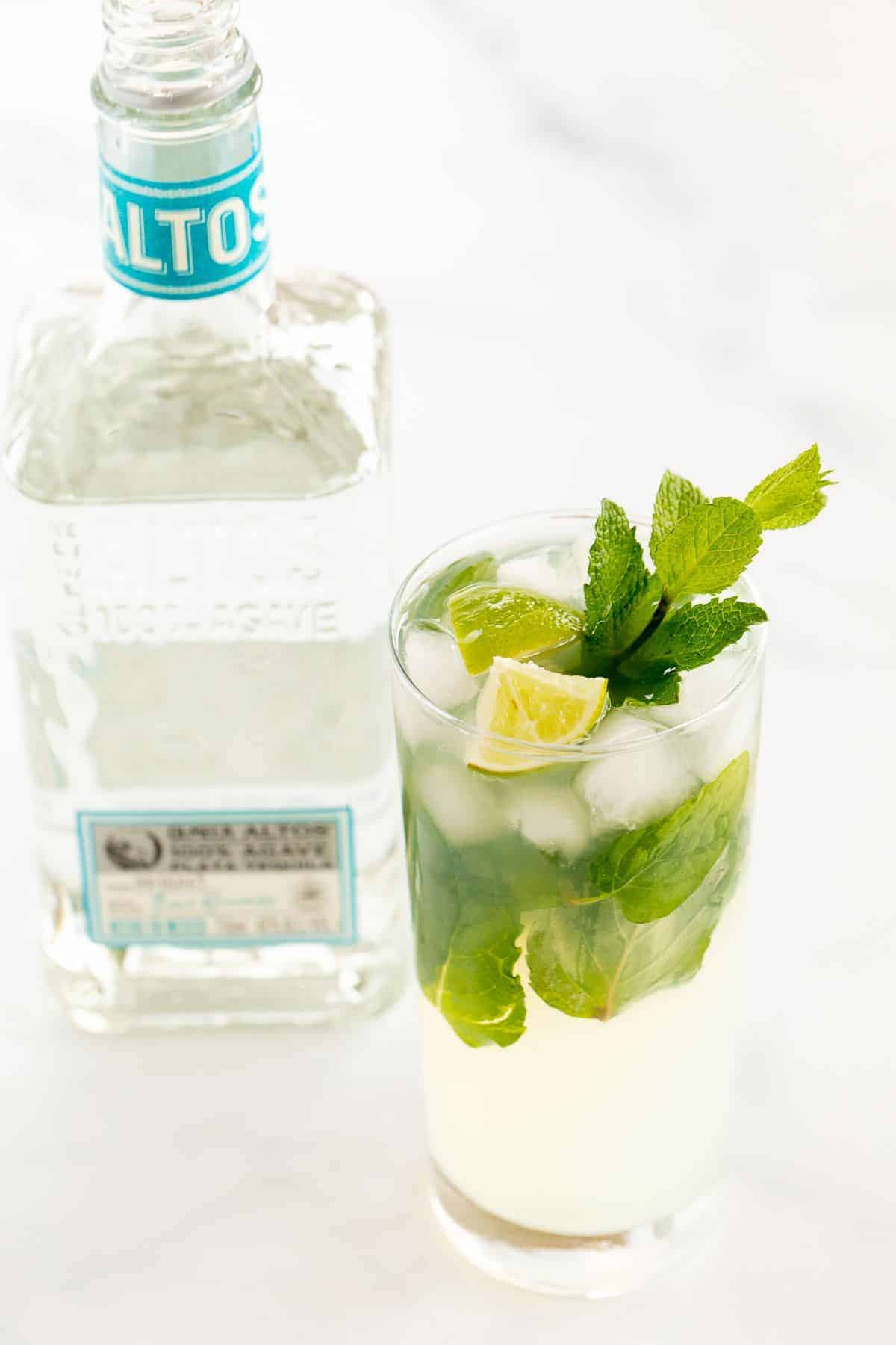 A tequila mojito in a clear glass on a white surface, garnished with wedges of lime and fresh mint, bottle of tequila in the background.