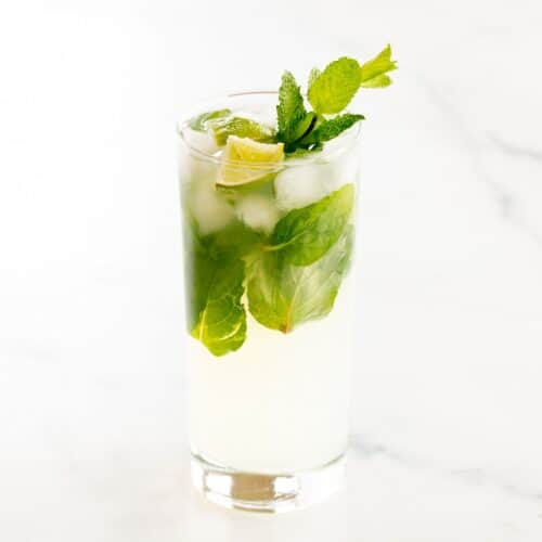 A tequila mojito in a clear glass on a white surface, garnished with lime wedges and fresh mint.