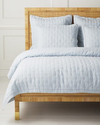 blue tufted quilt on rattan bed