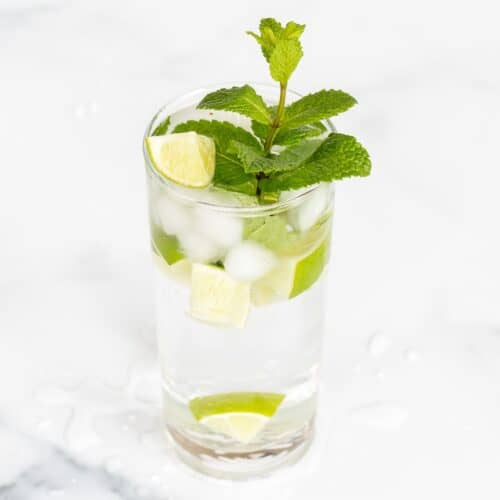A clear glass full of a virgin mojito recipe on a marble surface.