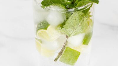A clear glass full of a non alcoholic mojito recipe on a marble surface.