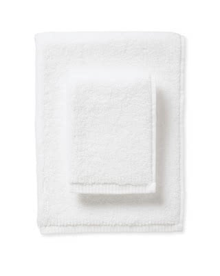 white bath towels stacked on top of one another