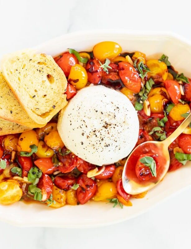 Burrata Bruschetta in a white serving bowl, crostini and a gold spoon to the side.