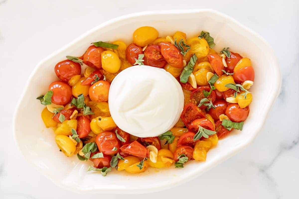 Roasted cherry tomatoes and basil topped with burrata cheese in a white serving dish.