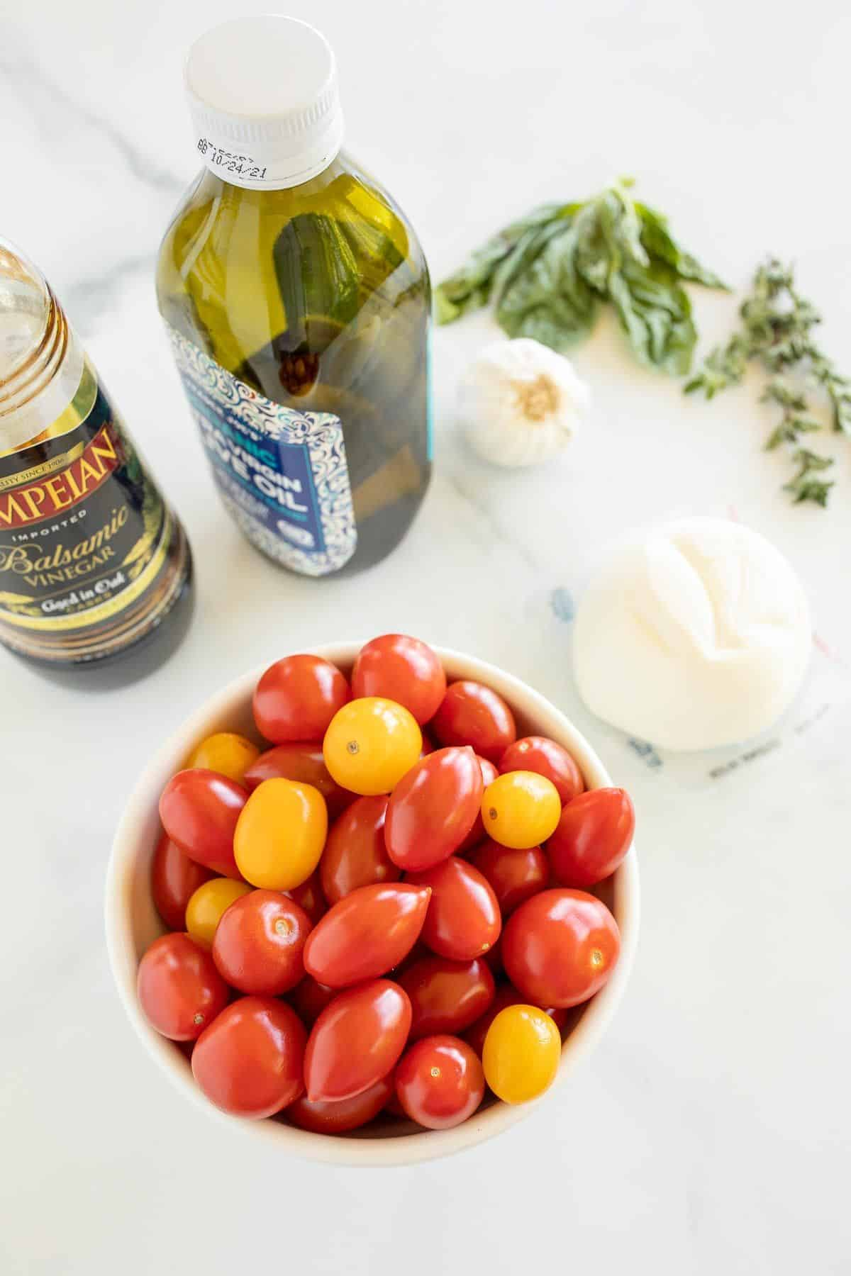 Ingredients for a baked burrata recipe, including cherry tomatoes, olive oil, burrata cheese and more.