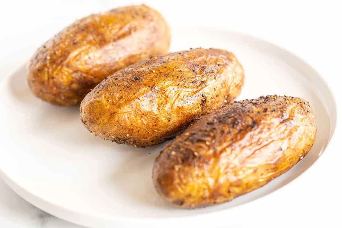 Crispy grilled baked potatoes on a white plate.