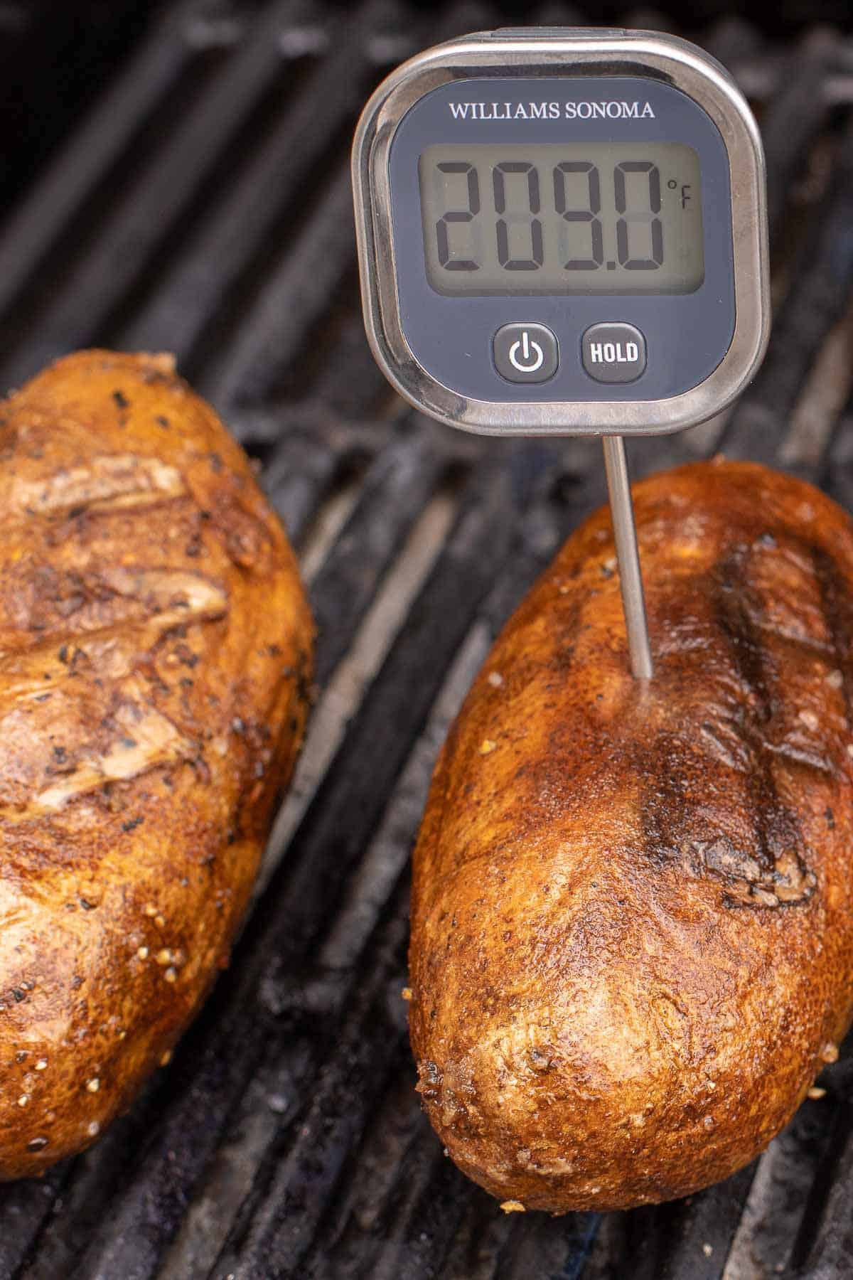 Grilled baked potatoes on a grill grate, one has a digital thermometer inside.