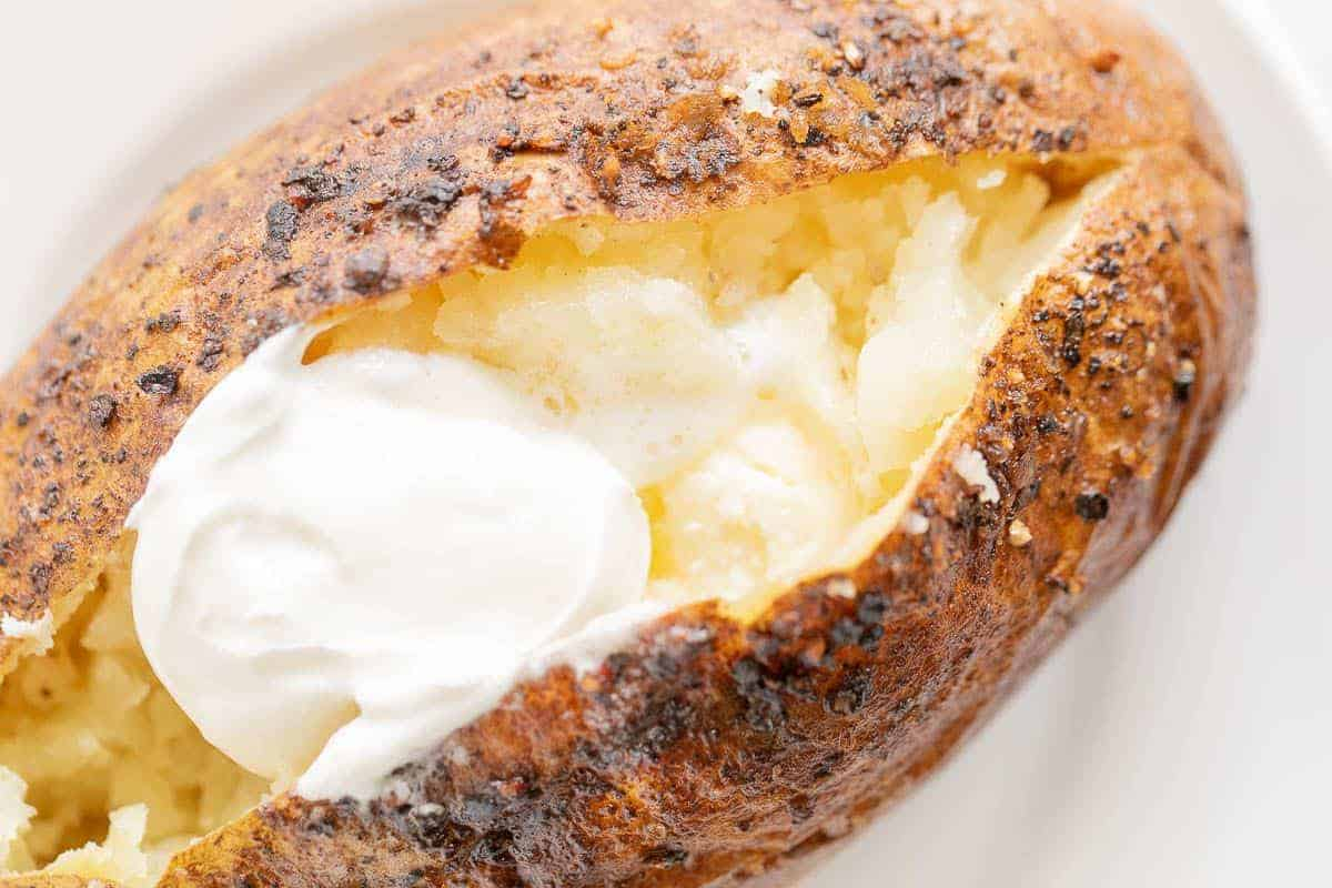 A grilled baked potato sliced open and topped with sour cream.