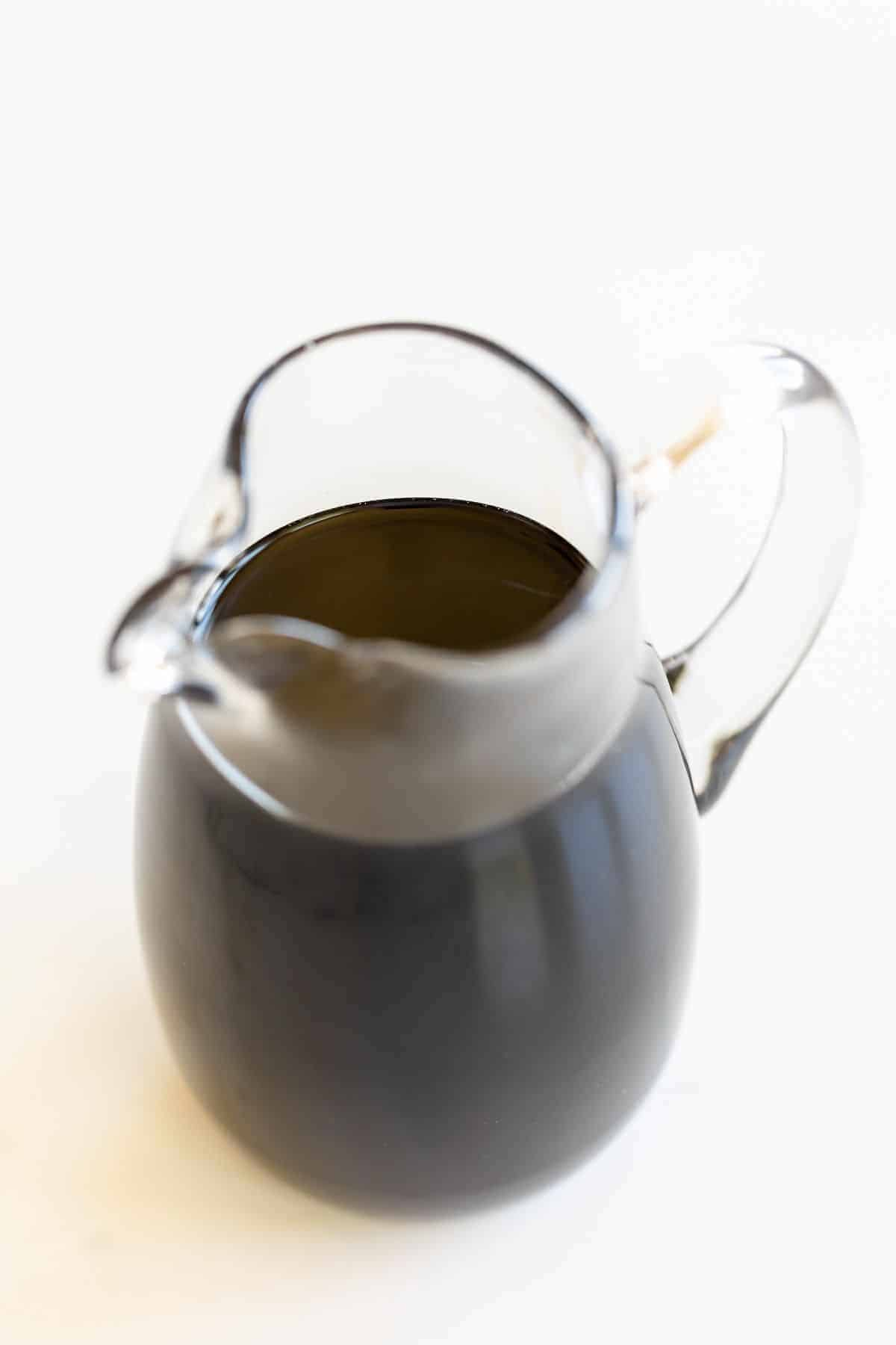 A clear pitcher full of balsamic glaze, on a white surface.
