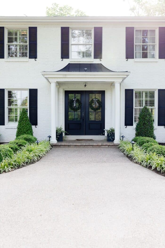 A colonial brick house painted in Benjamin Moore Simply White with black shutters.