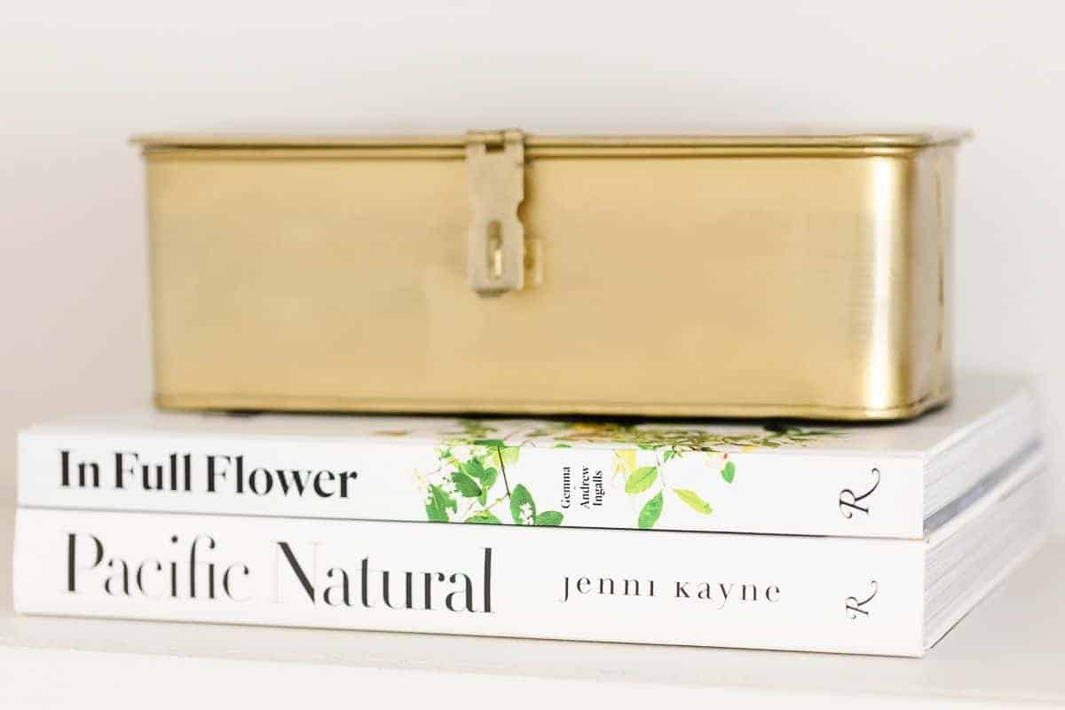 White books with a gold box on top for bookshelf styling.