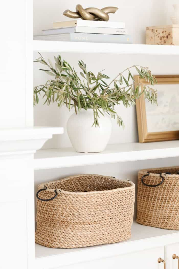 White Built in bookshelves with decor of baskets, white pottery and artwork.