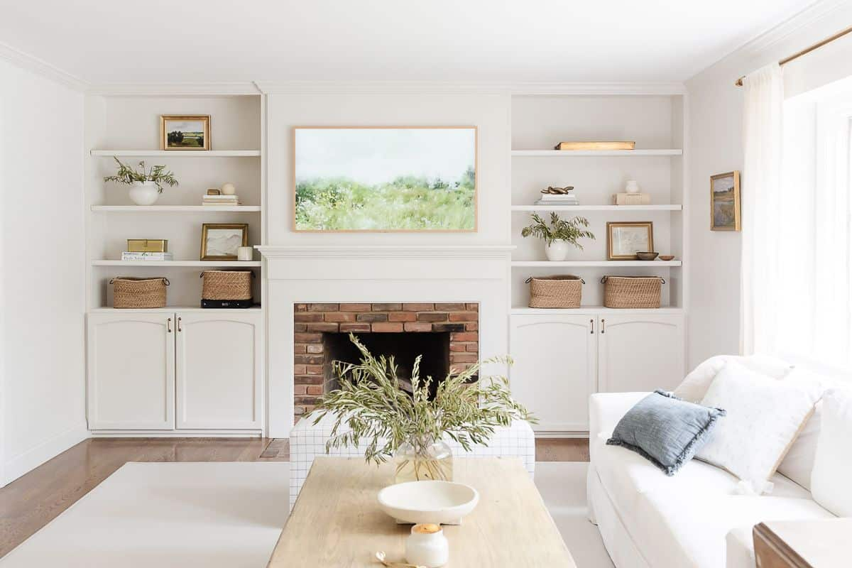 A white living room with bookshelf decor, and a brick fireplace surrounded by built ins,