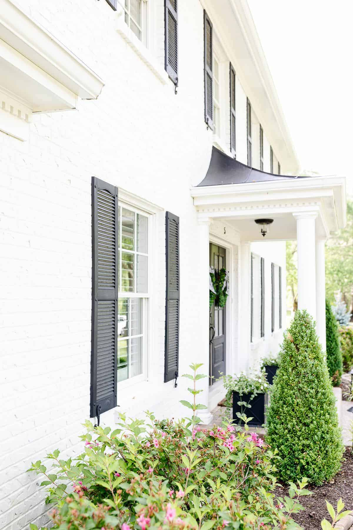 A white brick house with black shutters.