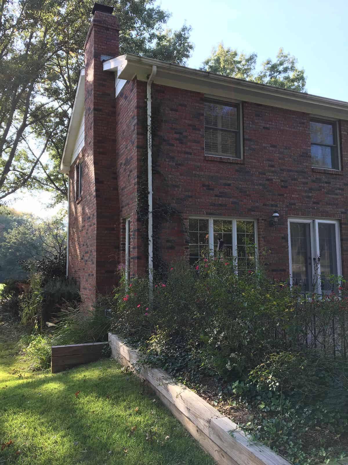 A dark brick house exterior before undergoing a paint transformation.