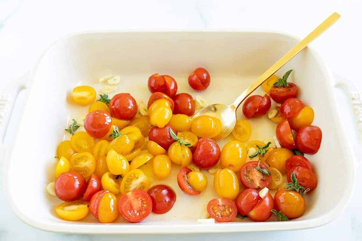 Diced cherry tomatoes in a white baking pan, gold spoon to the side.