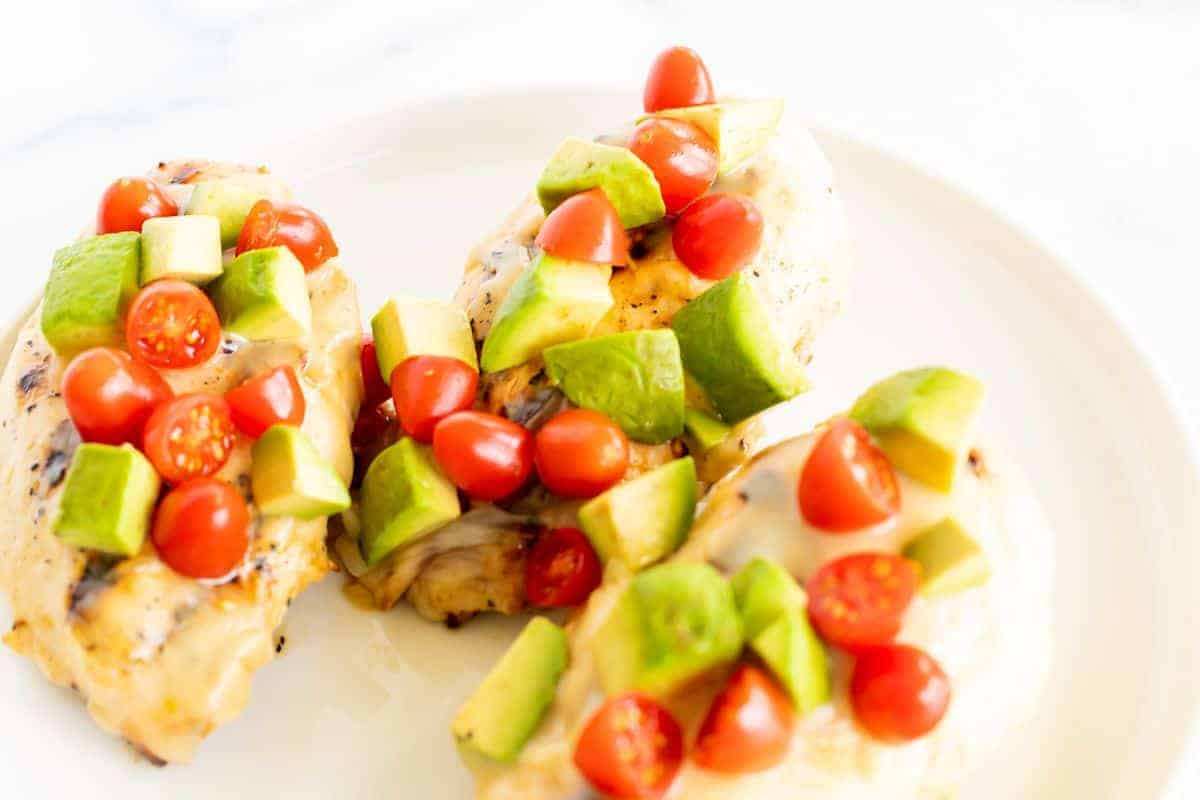 California chicken grill on a white plate, topped with diced avocado and tomato.