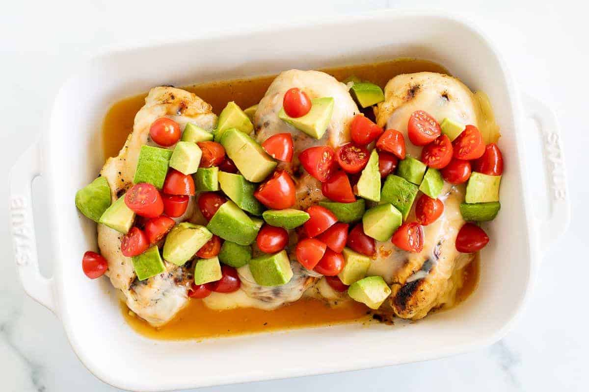 A white baking pan filled with California chicken, topped with diced cherry tomatoes and avocado.
