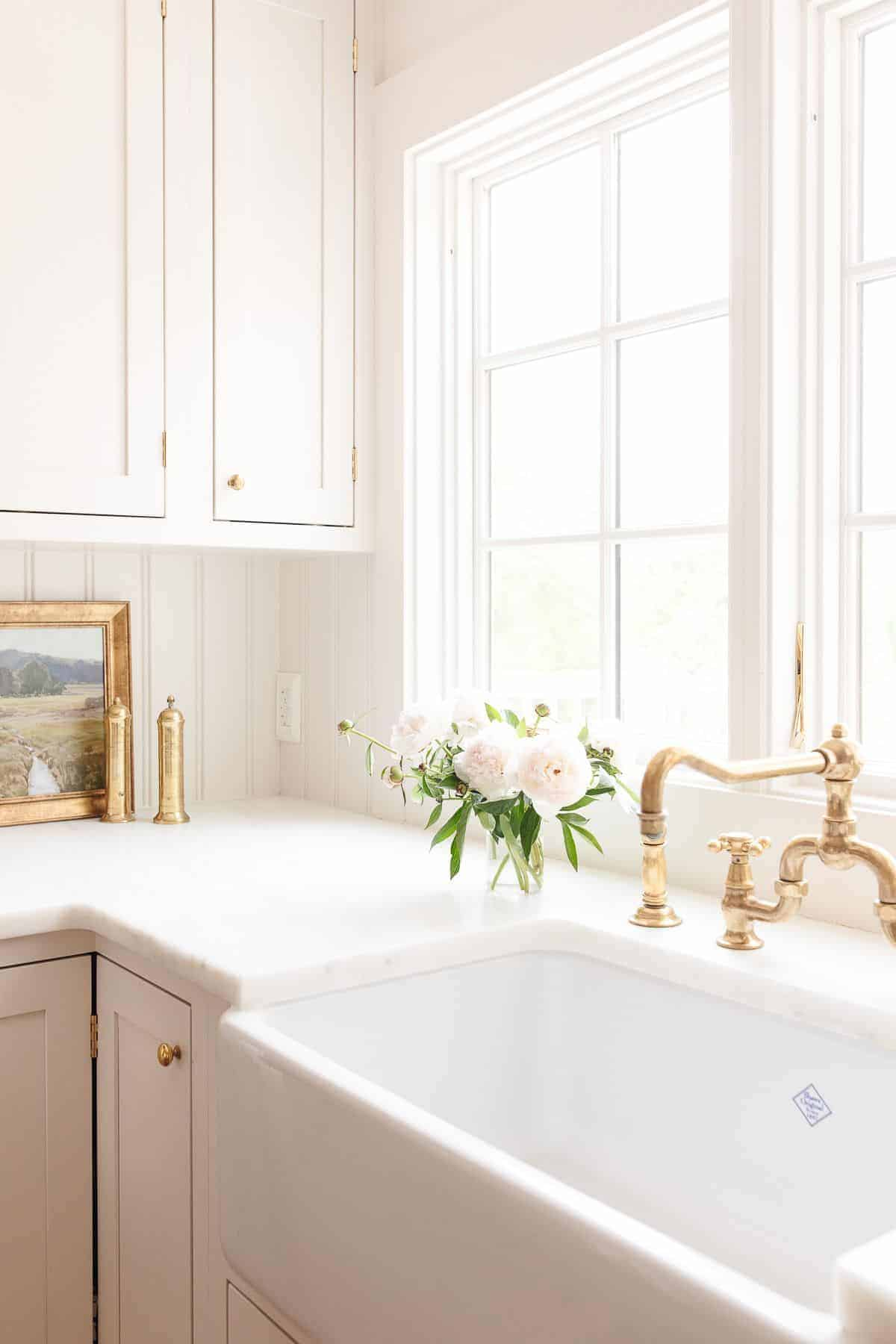A cream-colored kitchen with a farm sink and custom cabinets.