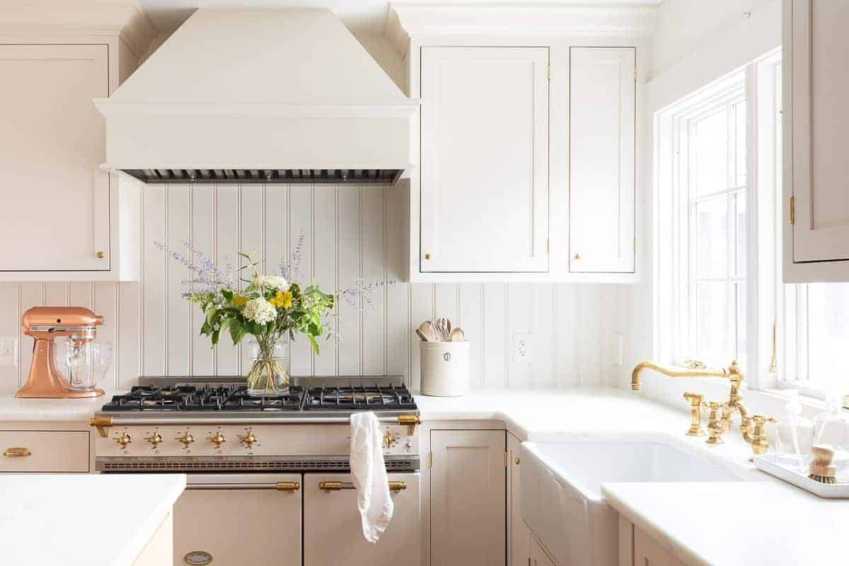 A cream kitchen with a farm sink, french range, and custom kitchen cabinets.