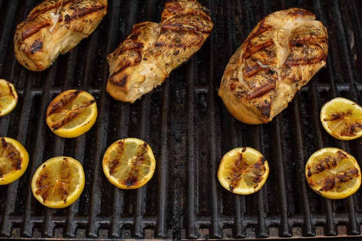 Greek chicken breasts on a grill, slices of lemon being grilled too.