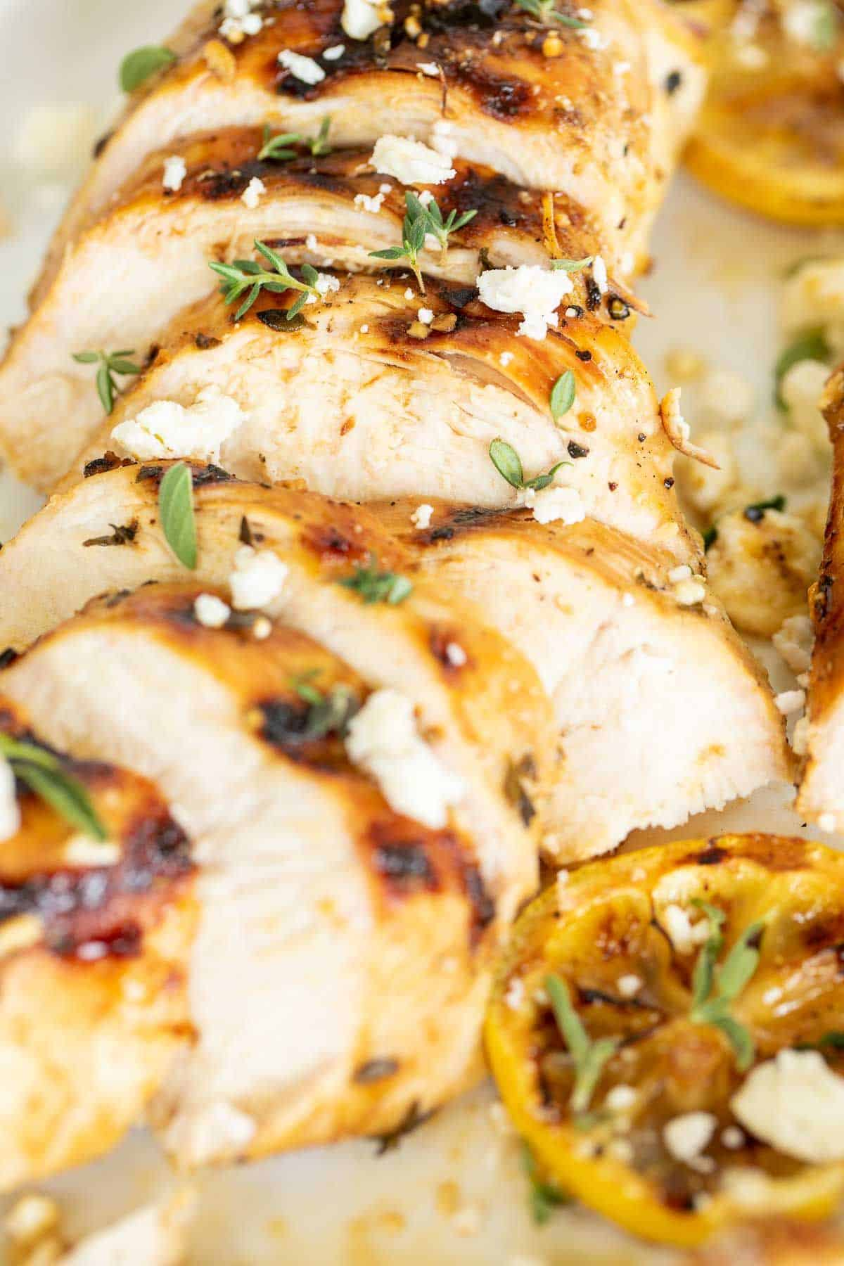 Slices of Greek marinated chicken on a white surface, grilled.