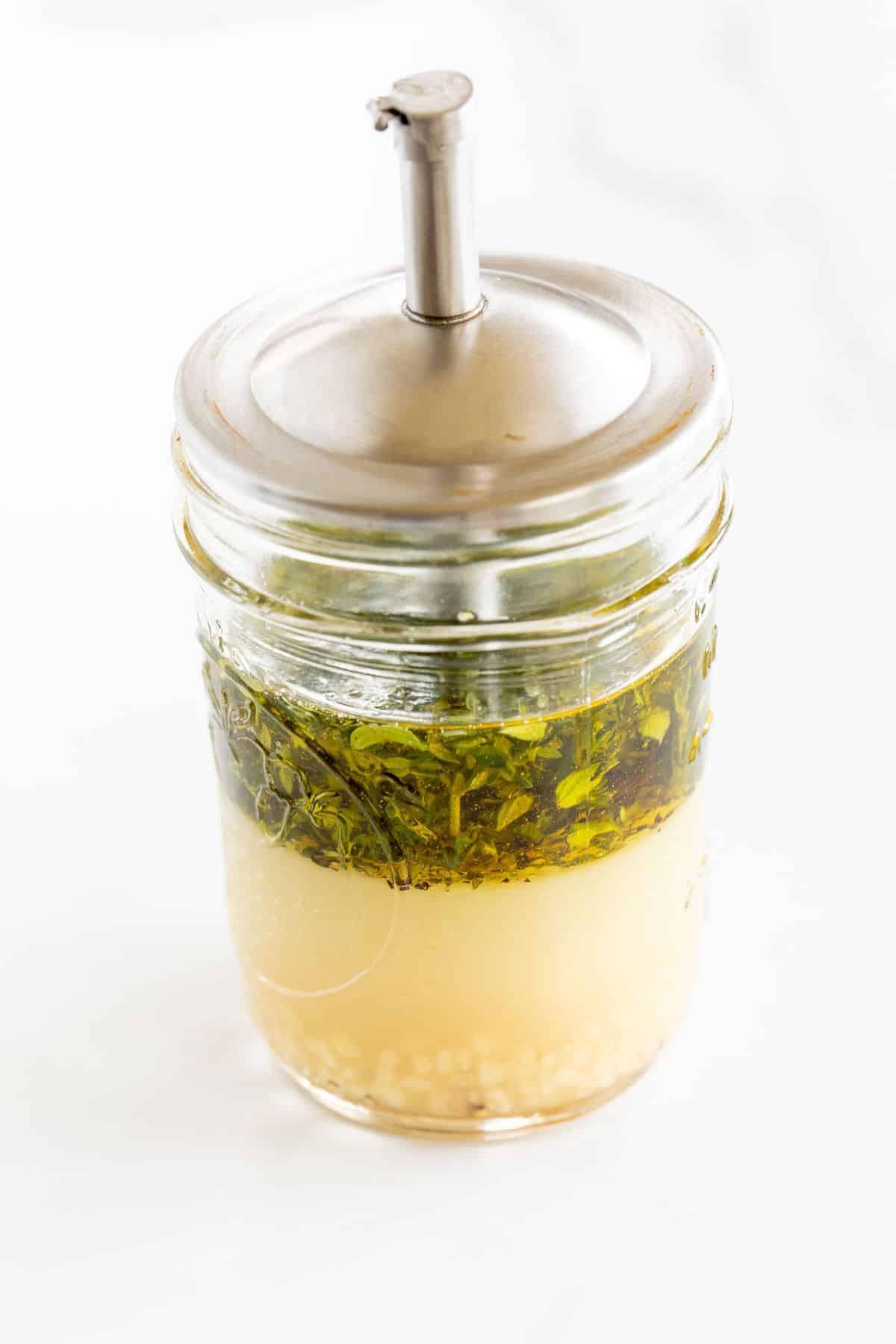 A clear glass mason jar full of Greek chicken marinade.