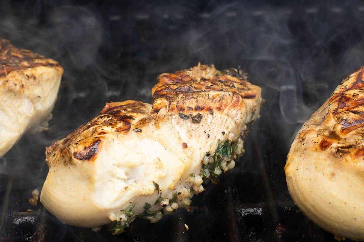 Greek chicken breasts on a grill.