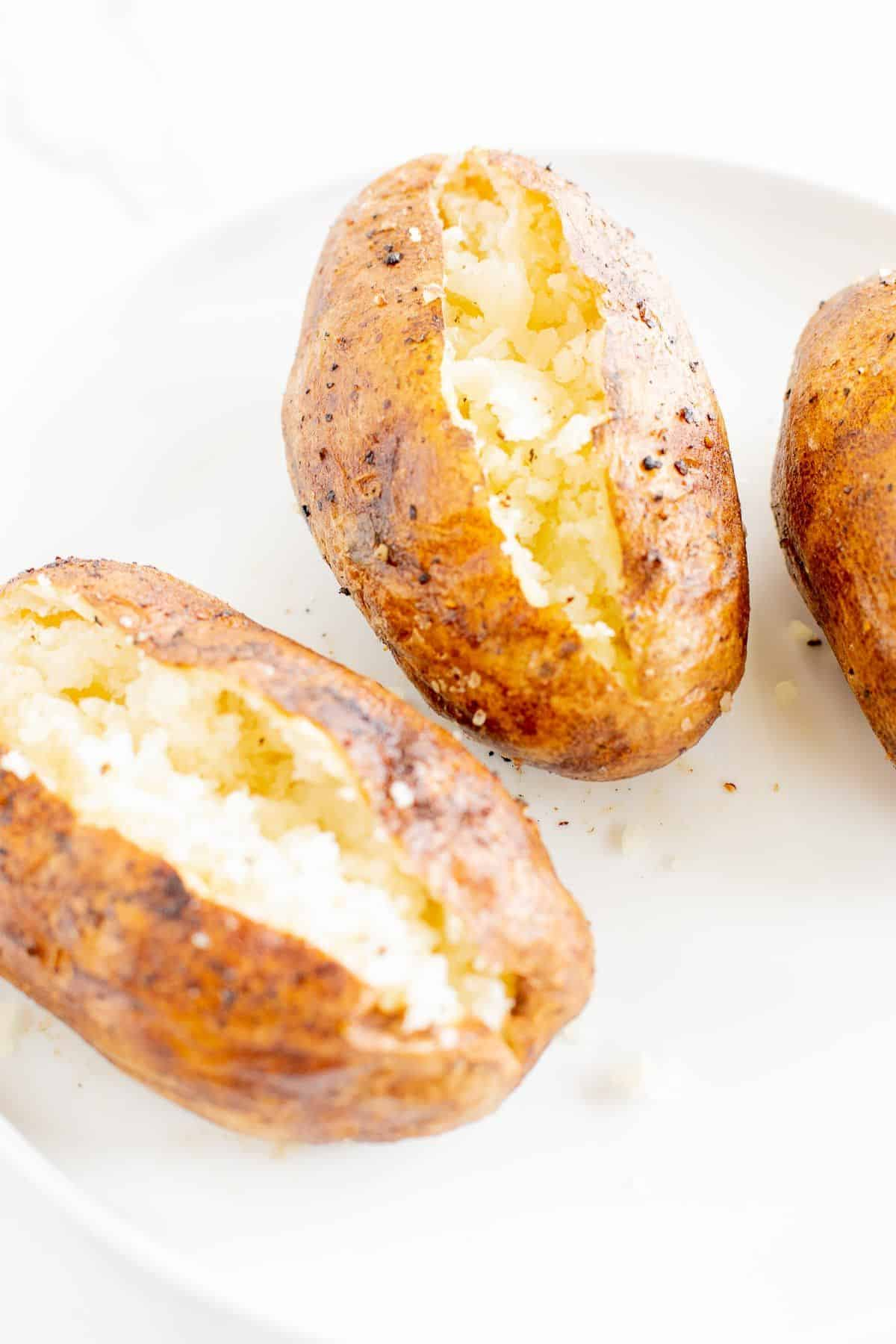 grilled baked potatoes sliced open and placed on a white surface.