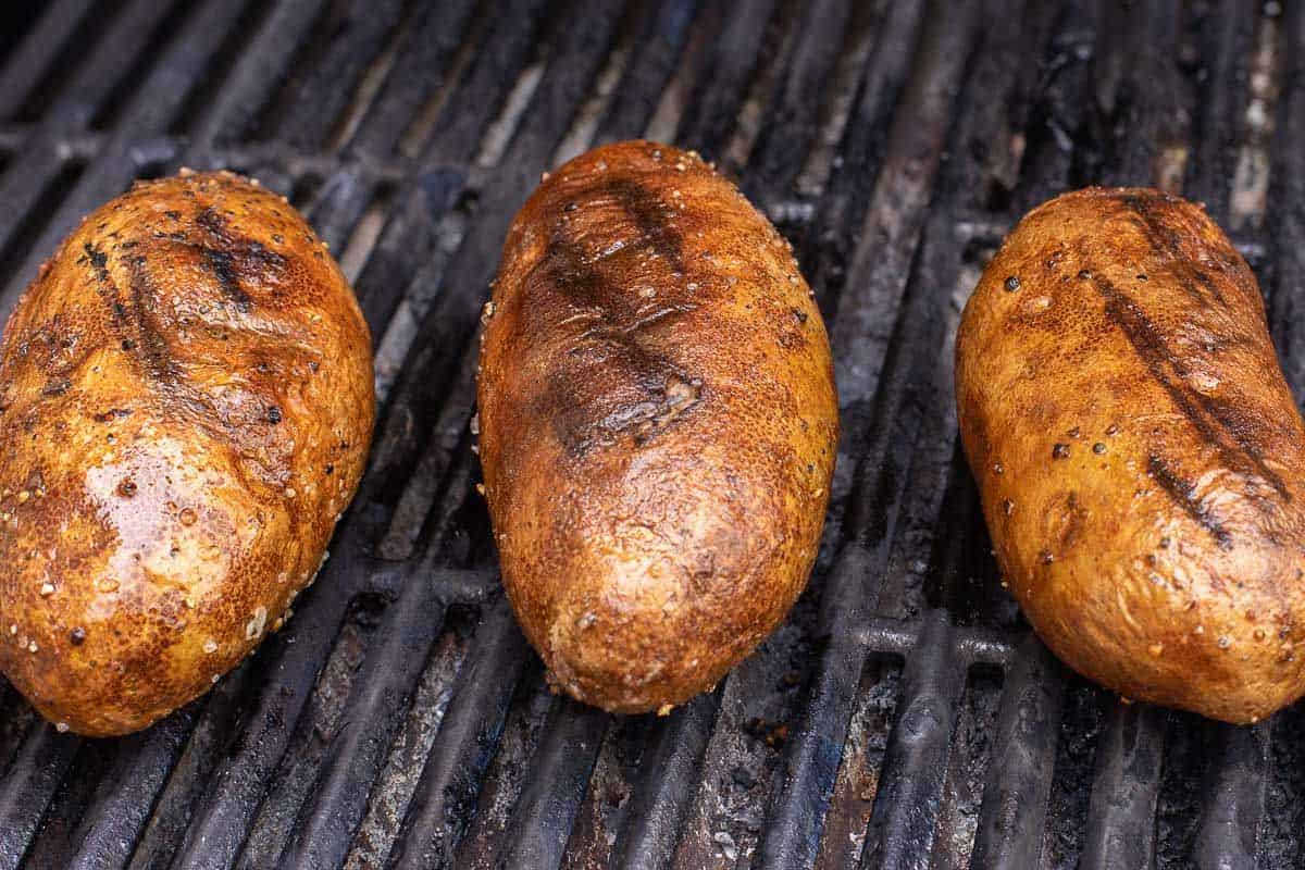 Grilled baked potatoes on a grill grate.