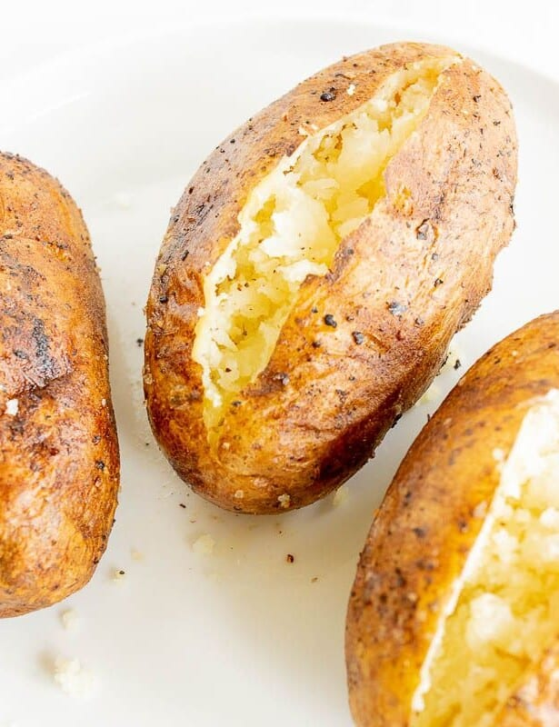 grilled baked potatoes sliced open and placed on a white plate.