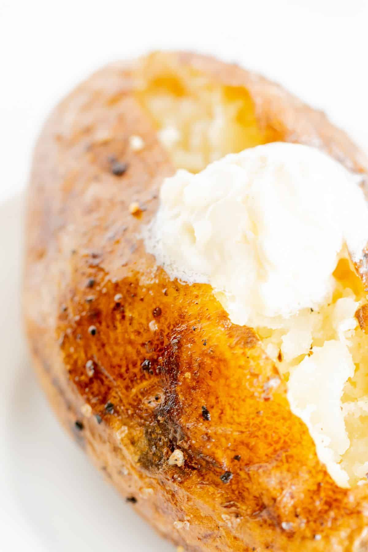A single BBQ baked potato on a white plate, topped with butter and sour cream.
