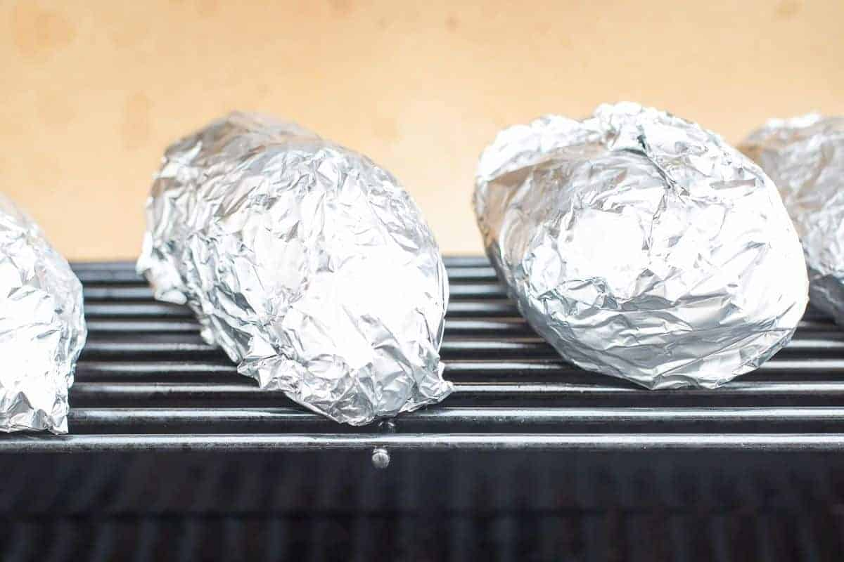 Grilled baked potatoes in foil on a grill grate.