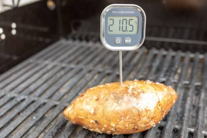 A sweet potato on a grill with a digital thermometer stuck in it.