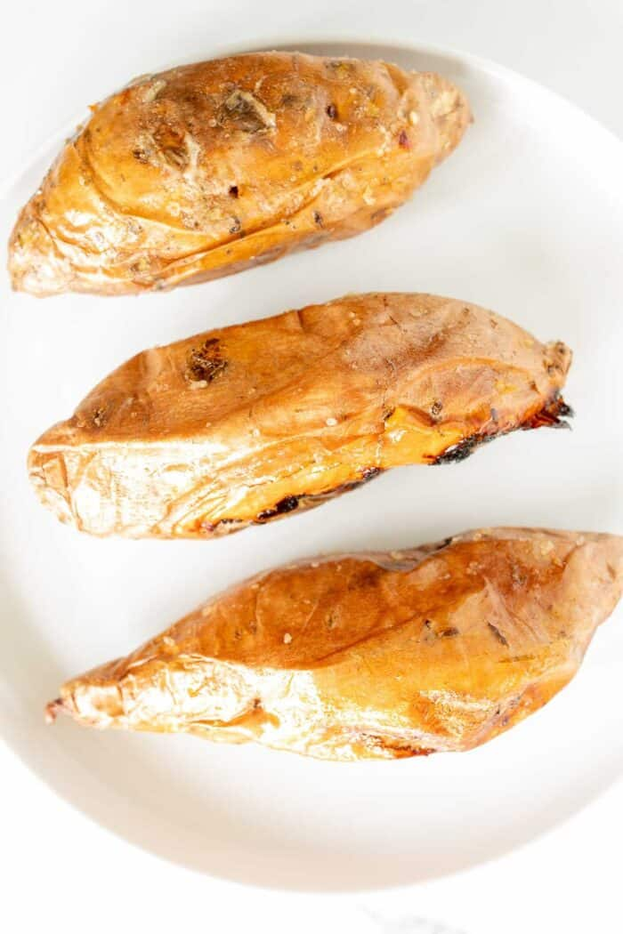 Grilled sweet potatoes on a white plate.