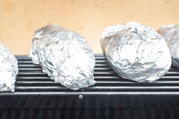 Grilled sweet potatoes in foil on an outdoor grill.