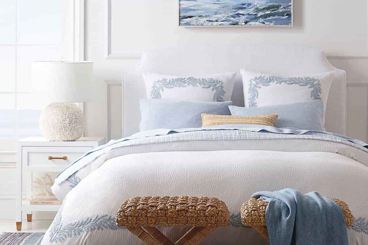 A white guest room with blue and white guest bedding on the bed.