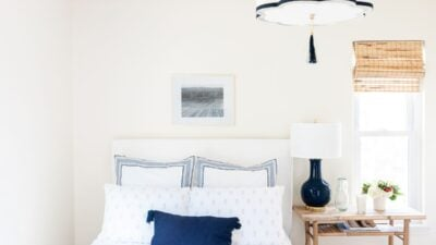 A navy and white guest bedroom with white guest bedding.