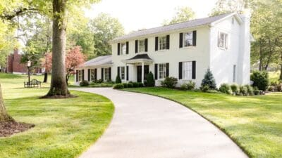 A colonial white brick house with a curved driveway.