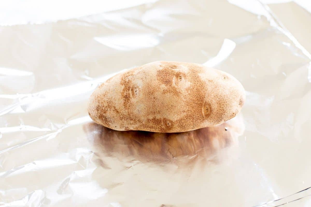 A single russet potato laid on a sheet of aluminum foil.