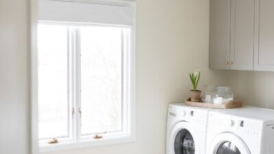 A laundry room with white washer and dryer, gold light fixture and white walls and white baseboards
