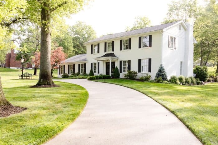 A colonial brick house painted in Benjamin Moore Simply White.